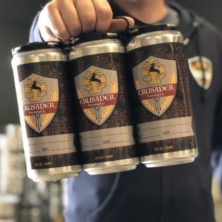 close up of a man holding a six pack of Crusader beer